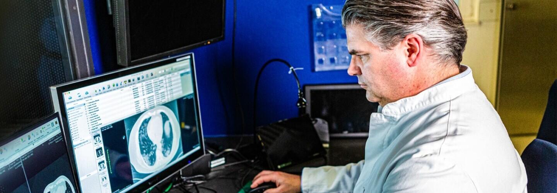 Un uomo siede di fronte allo schermo di un computer che mostra immagini di diagnostica ospedaliera.