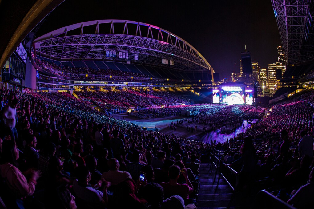 A full stadium with a concert stage at one end.