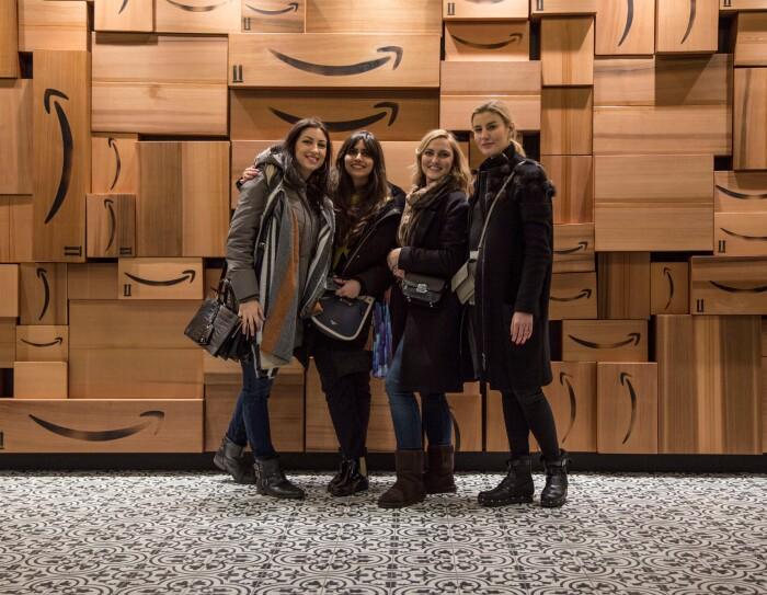 Quattro ragazze sorridono di fronte a un muro di scatole Amazon. Sono Monika, Urte, Francesca e Ankita, vincitrici dell'Amazon Design Award, quattro studentesse del Master in Interior Design dello IED Milano hanno vinto gli Amazon Design Awards, una competizione in cui si chiedeva ai corsisti di ripensare i depositi di smistamento Amazon con uno sguardo alla praticità e al comfort dei dipendenti.