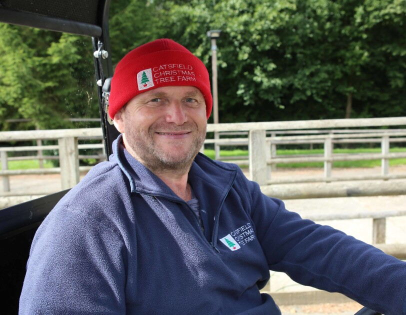Clive Collin, owner of Catsfield Christmas Tree Farm, sitting in a buggy outside of his Christmas tree farm. He is wearing a beanie hat with his company logo on it.