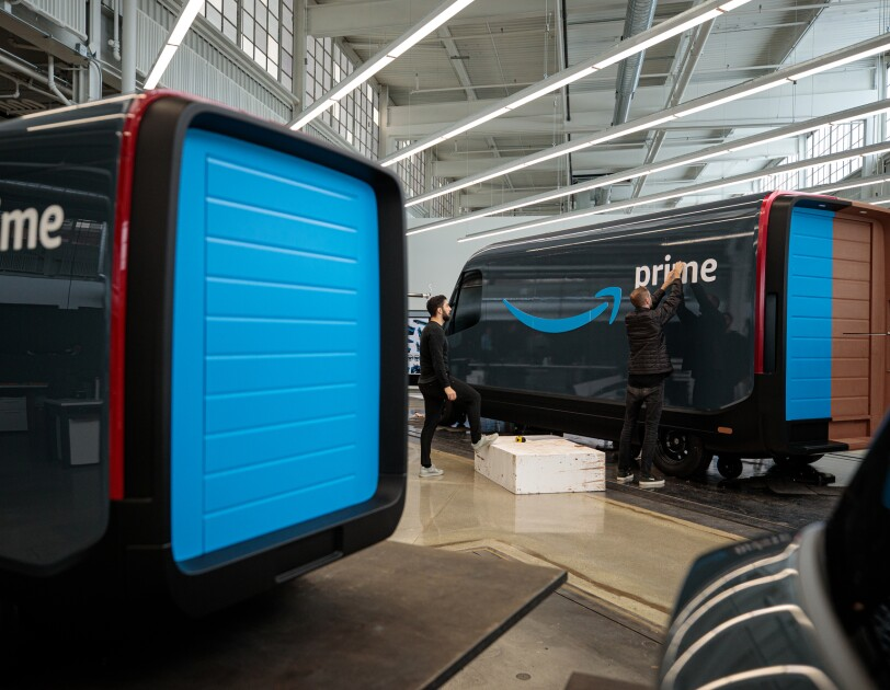 A worker applies a Prime logo to a model of an Amazon delivery vehicle.
