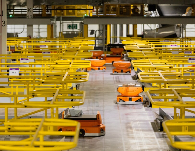 Orange robots in a large warehouse space.
