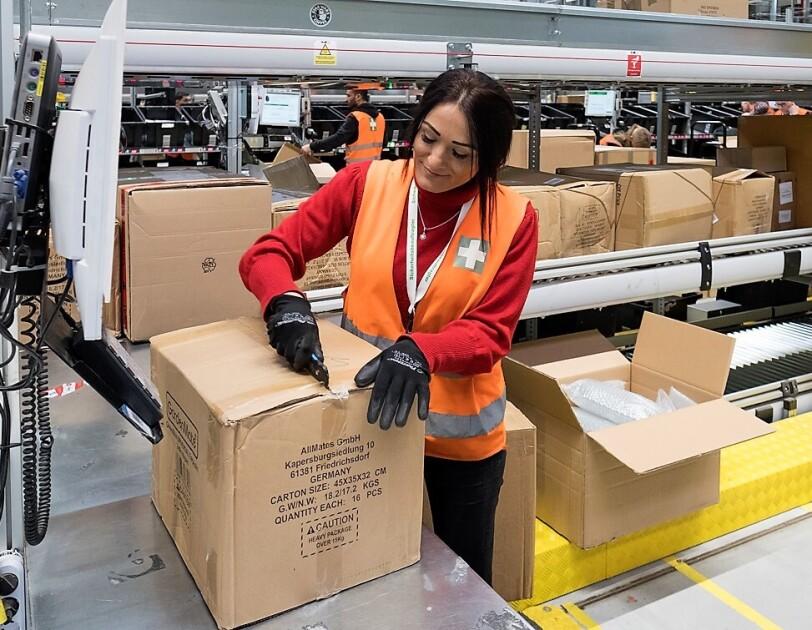 Eine Mitarbeiter, die Sicherheitshandschuhe trägt, öffnet mit einem Cutter eine Kartonage.
