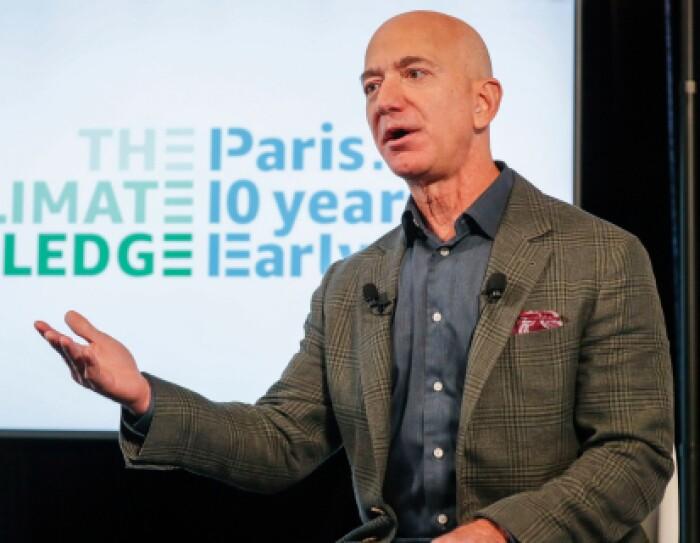 De fondo el cartel the The Climate Pledge, Paris 10 years early. Jeff Bezos en primer plano con una mano levantada. Una amerciana verde y gris a cuadros y una camisa azul. En la americana lleva un pañuelo rojo.