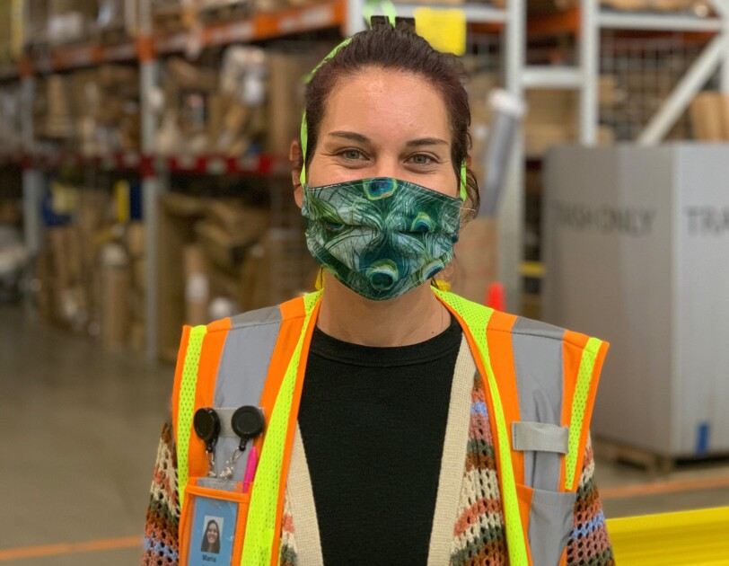 A woman wearing  a safety vest and a mask that covers her mouth and nose stands in a space with tall shelves in the background.