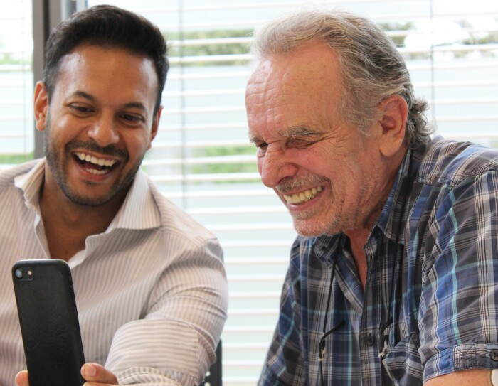 Ein jüngerer zeigt einem älteren Mann sein Smartphone. Beide lachen.