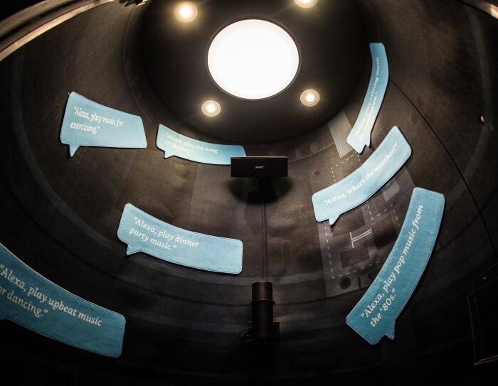 Día Europeo de la Innovación 2018. Construcción cilíndirca de color negro con cuatro focos que iluminan mensajes en ingles en bocadillos de cómic que hablan sobre Alexa. Uno de los mensajes es así: Alexa interpreta música de los '80, etc.