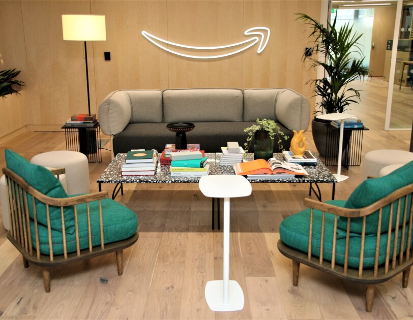 A view of the sitting area in the Amazon Manchester head office. There is a sofa and two armchairs surrounding a table which is covered in books, plants and ornaments.