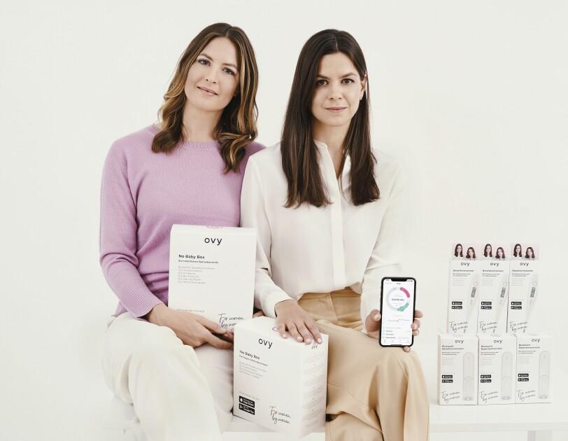 Zwei Frauen mit dunklen Haaren halten ein Handy mit der Ovy App in der Hand und lächeln in die Kamera.