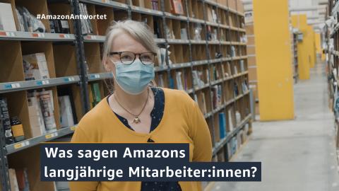 Eine Mitarbeiterin steht im Amazon Logistikzentrum. Im Hintergrund sieht man die Regale mit Produkten.