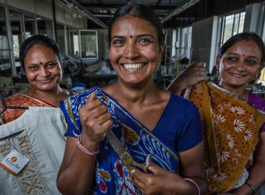Women proudly hold up Amazon Saheli products and materials.