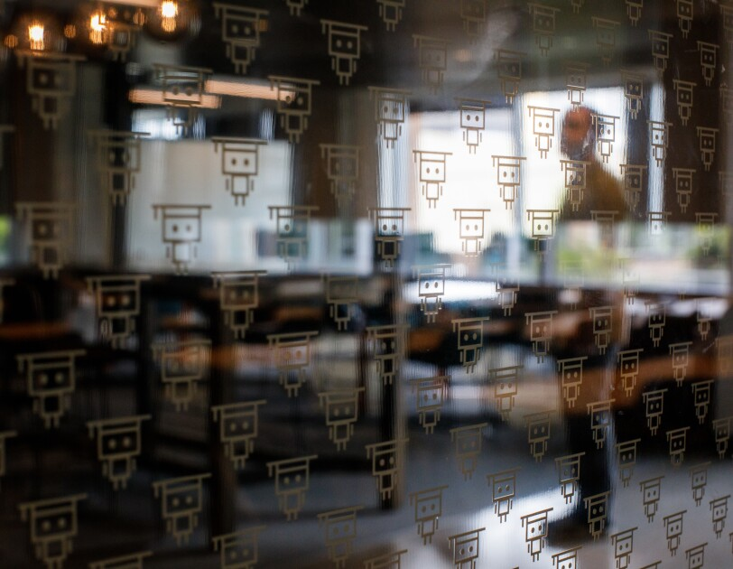 A glass wall decorated with a repeating patttern of a simple cartoon figure wearing a graduation cap.