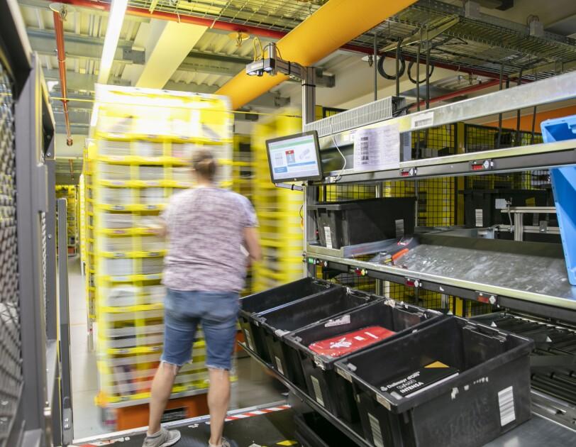 eine Mitarbeiterin befüllt ein gelbes Regal mit Artikel, Unter dem Regal sieht man den Roboter.