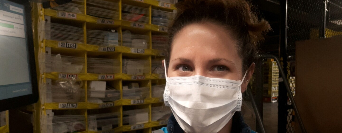 A woman in a safety mask stands with shelving behind her.