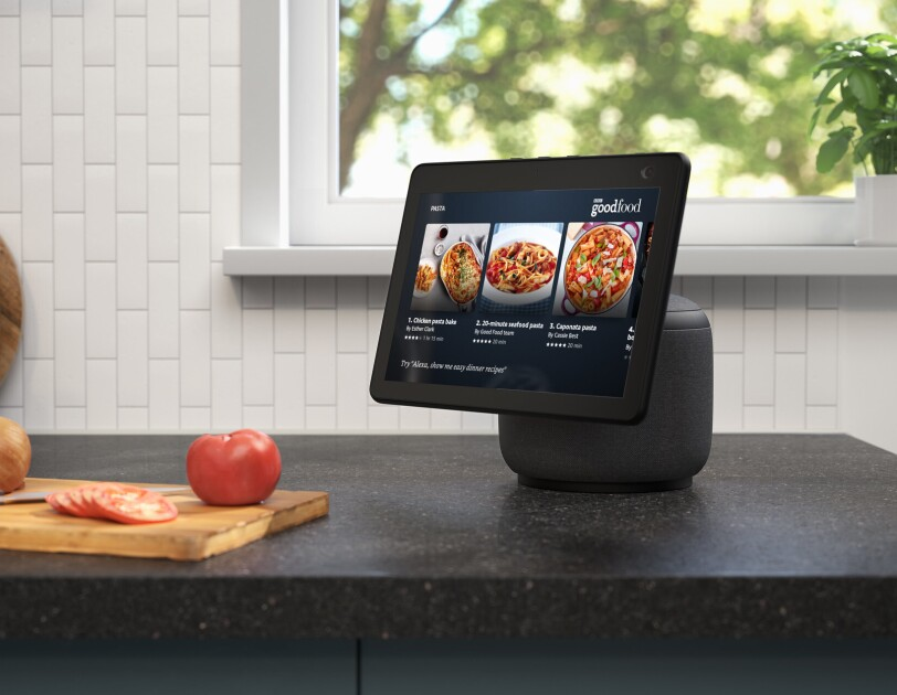 An image of the new Echo Show 10 on a kitchen counter. The device is showing recipes on BBC goodfood and next to the device there is a chopping board with tomatoes and onions.