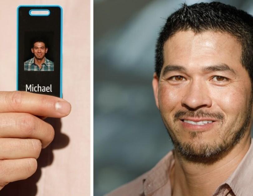 Pracownik Amazon trzymający swój identyfikator z niebieską ramką i czarnym tłem.