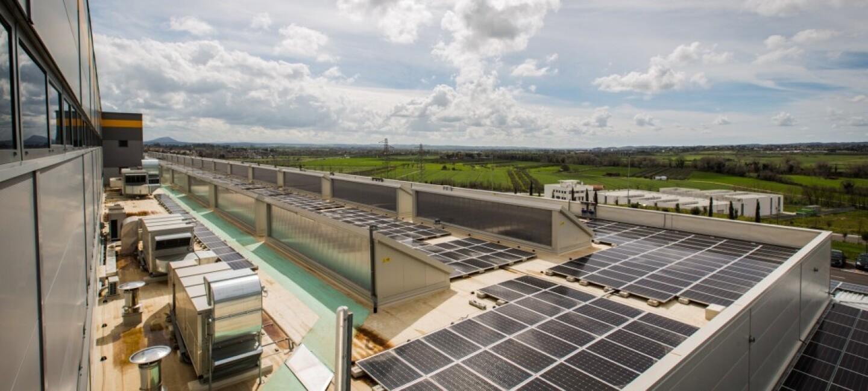 En primer plano aparece el tejado de un centro logístico con placas solares. Al fondo un paisaje de campos verdes y el cielo azul con nubes blancas.