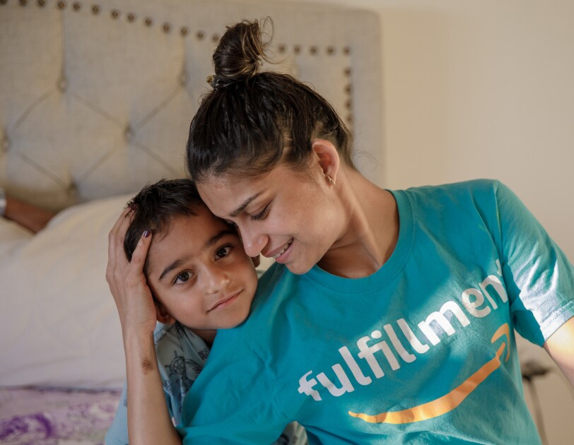 "A young boy leans on the shoulder of a woman who cradles the side of his head with one hand. The woman has her hair up and wears a T-shirt with the Amazon smile logo and the word ""fulfillment."""
