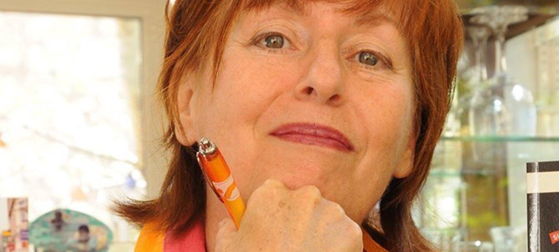 Portrait resserré d'Alice Quinn, un stylo à la main. Son stylo orange est assorti à sa tenue. En arrière-plan des étagères avec des verres.