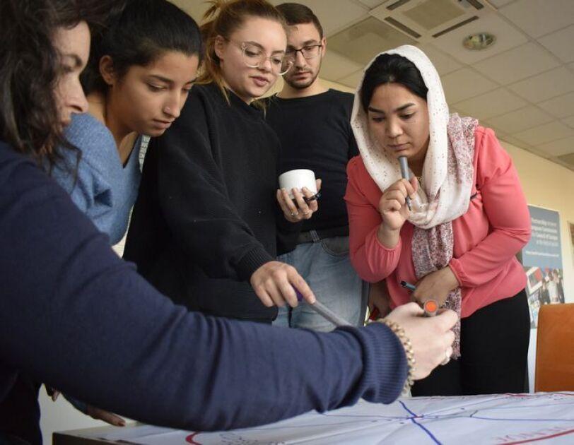 Junge Menschen verschiedener Nationalitäten besprechen ein Plakat.