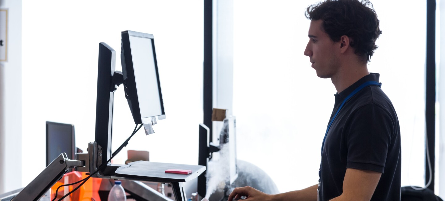 Man working on his computer at a standing desk