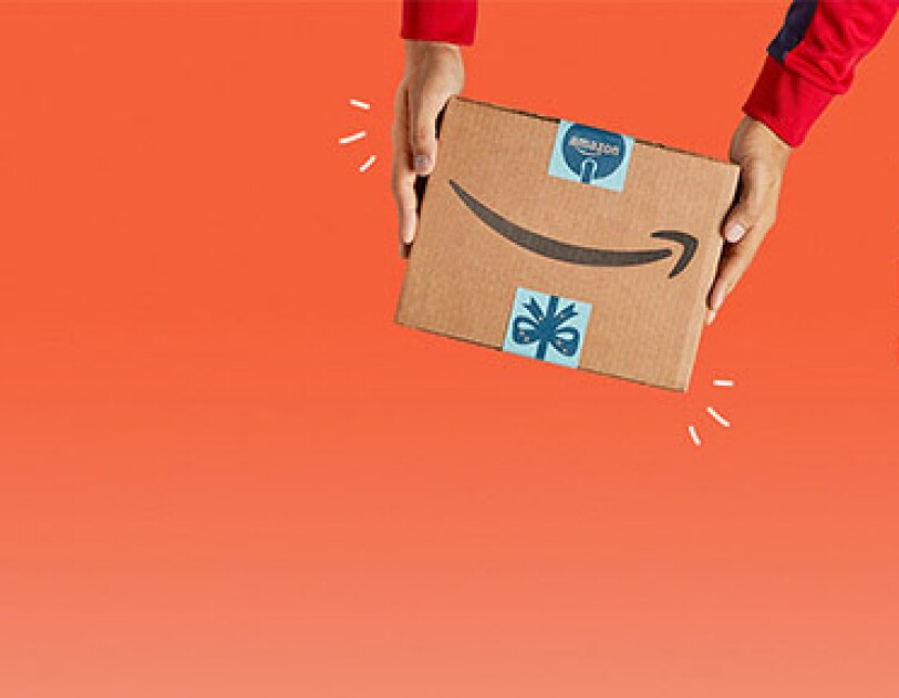 Black-Friday_Cyber-Monday Amazon Paket vor orangenem Hintergrund