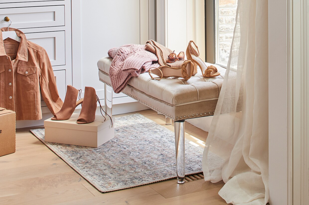 A lifestyle image of a Prime Wardrobe box with a blush purse sitting on top of it. To the right, a pair of open-toed heels sit on a shoe box, and a jacket hangs from a drawer pull, on a hanger. An upholstered bench holds another pair of heels, a sweater, scarf and sunglasses.
