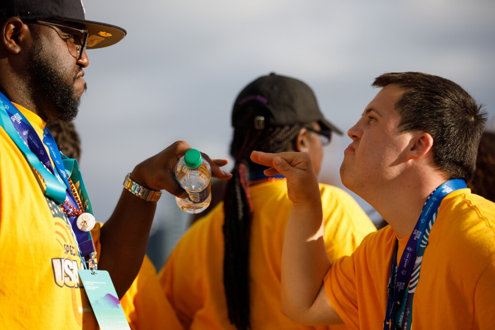 """Two male closing ceremony attendees appear to jokingly """"face off"""" as they face one-another."""