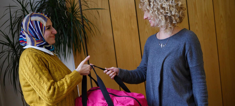 Eine bedürftige Mutter erhält eine Baby Bag von der Organisation.  Ds Bild zeigt, wie Maria Herzog die Tasche an die Mutter übergibt.