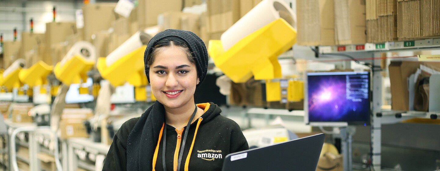 Amazon apprentice, Sunha Zulfiqar, pictured holding a laptop and smiling at the camera with fulfilment centre packing stations in the background.