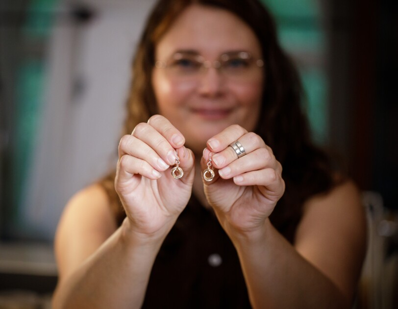 A woman holds a pair of earrings.