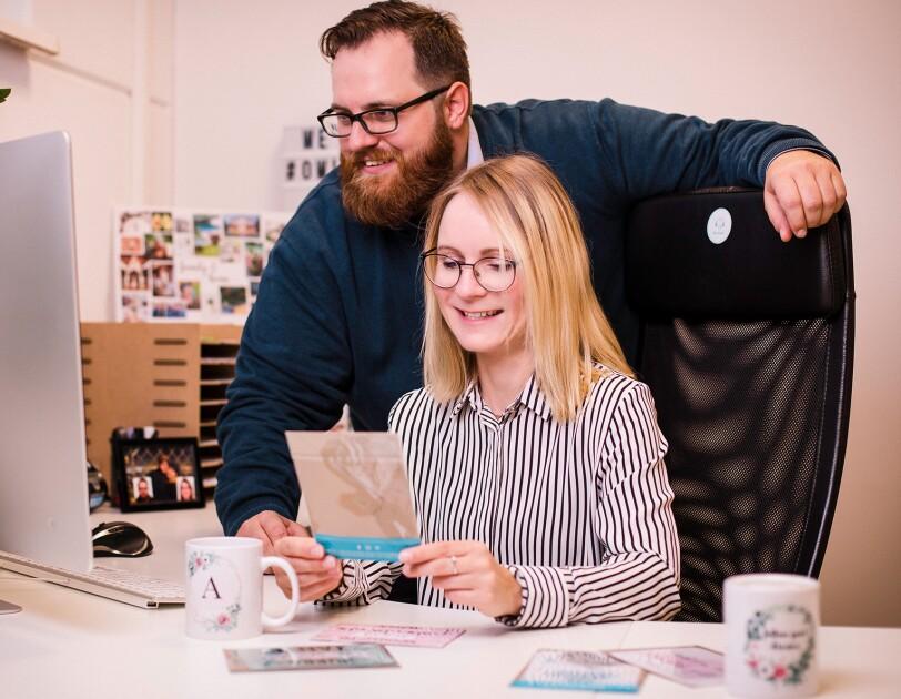 Eine Frau und ein Mann sitzen und stehen vor einem Computerbildschirm. Sie lächeln beide und schauen in den Bildschirm. Die blonde Frau hält eine Karte in den Händen, von der nur die Rückseite zu sehen ist. Sie befinden sich in einem Büro..