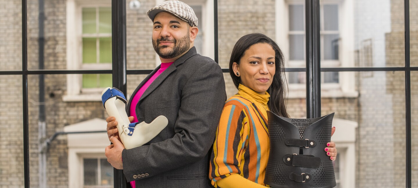 A photo of Naveed and Samiya Parvez, back to back, smiling and displaying two of the custom-made orthoses produced by their startup Andiamo: a device for the back and one for the ankle.