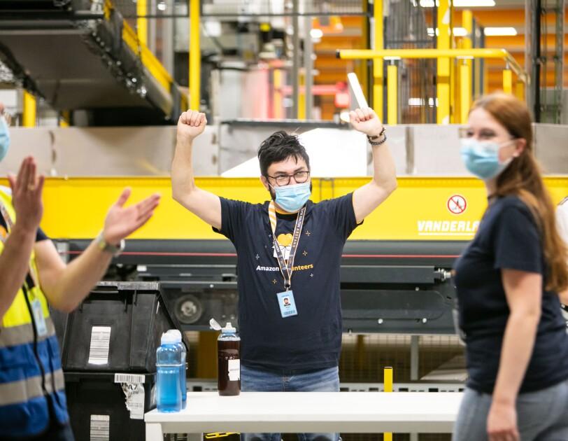 """Amazon Mitarbeiter mit Mundschutz und T-Shirt mit Aufschrift """"Amazon Volunteers"""""""