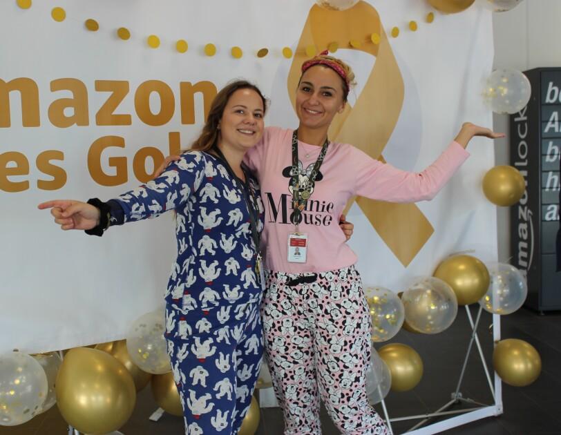 2 Mitarbeiterinnen im Schlafdress vor einer Fotowand mit Goes Gold