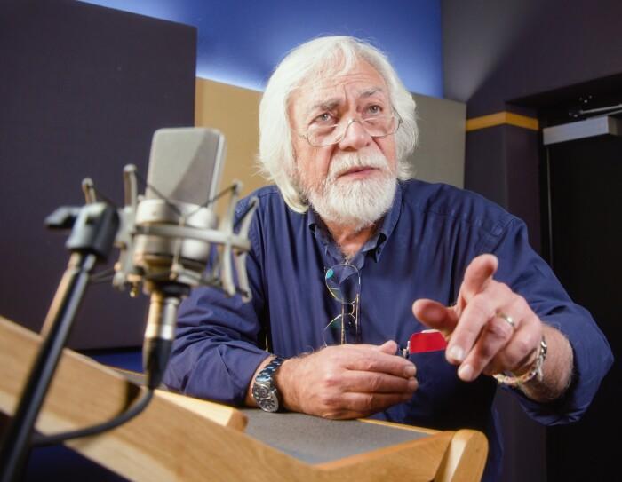 Ritratto di Gino La Monica, direttore di doppiaggio, attore e doppiatore, scattato in una sala di registrazione. In primo piano, fuori fuoco, un microfono. Gino La Monica è uno dei narratori più apprezzati di Audible.