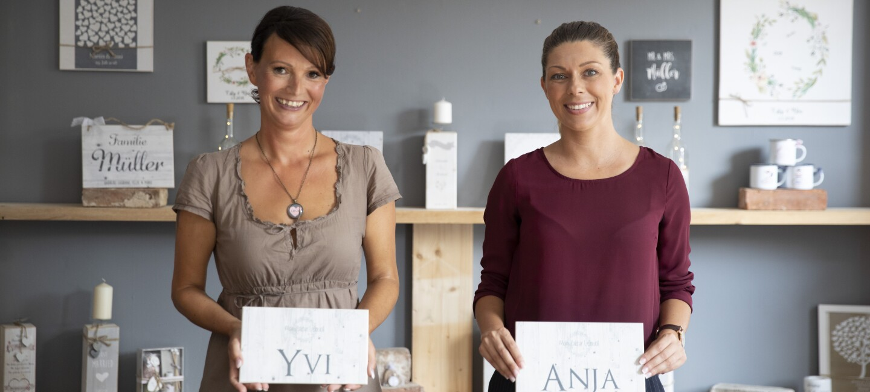 """Zwei Frauen mit dunklen Haaren stehen vor einer grauen Wand und schauen in die Kamera. In ihren Händen halten sie weiße Schilder mit ihren Namen """"Yvi"""" und """"Anna"""" in die Luft."""