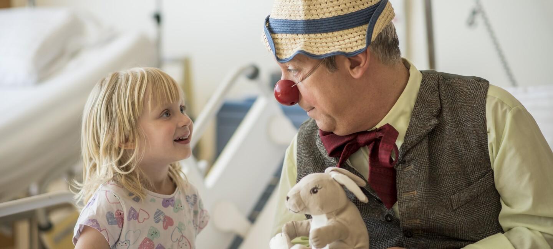Ein Clown der Roten Nasen, sitzt neben einem kleinen Mädchen im Krankenhausbett. Er trägt einen Strohhut und hält einen Plüschhasen in der Hand. Das Mädchen lacht ihn an.