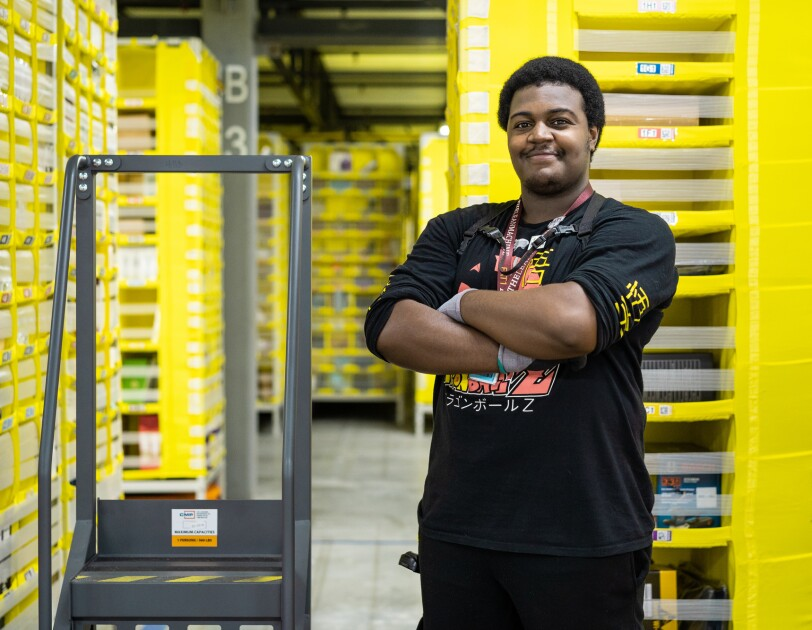 An Amazon employee, wearing a long-sleeve tee shirt, black pants and a lanyard stands with his arms crossed. Next to him is a step ladder. Behind him are tall yellow storage stacks.