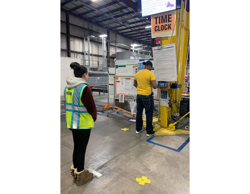 An Amazon associate stands at the time clock. Another associate stands 6 feet away, awaiting her turn.