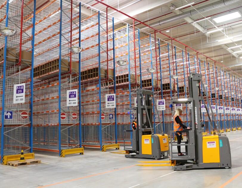 In einer Halle sind rund 30 Hochregale aufgebaut. Sie enthalten verschiedene Regalfächer aus Gittern. Die Fächer sind noch leer.