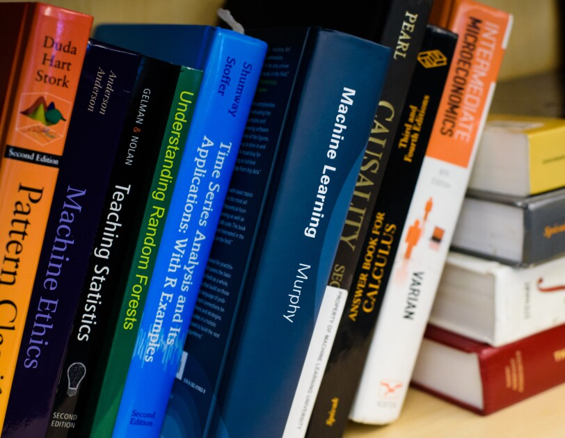 "Textbooks on a shelf. Titles include ""Machine Ethics,"" ""Teaching Statistics,"" and ""Understanding Random Forests."""