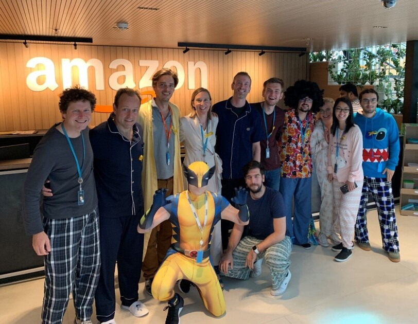 Amazon employees wearing pajamas surrounding our VP Retail Xavier Garambois (second from left) and super hero Wolverine #Pjammin #Letzgogold #deliveringsmile #Childhood cancer awareness.