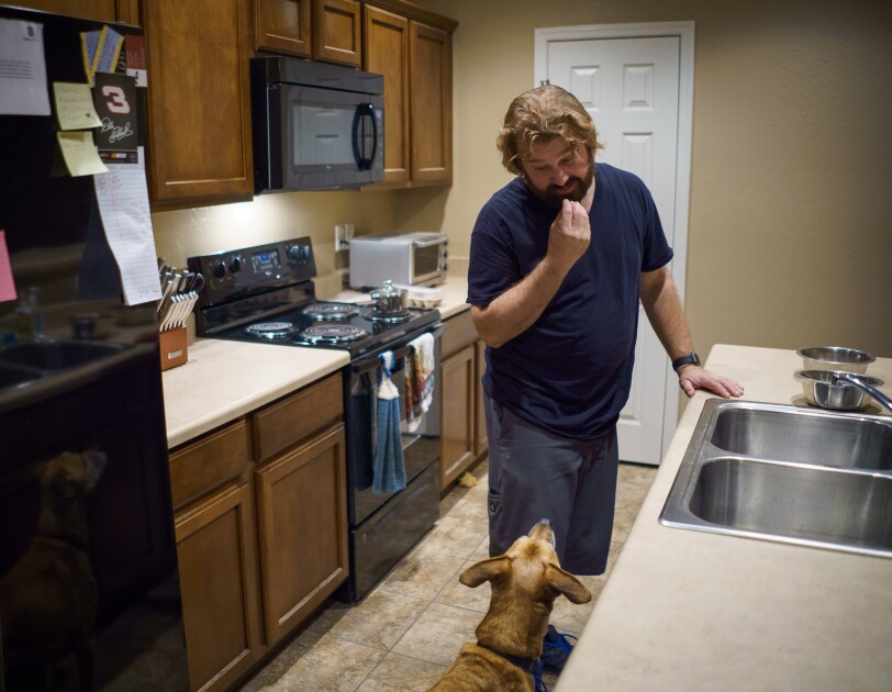 A man and dog stand inside a kitchen.