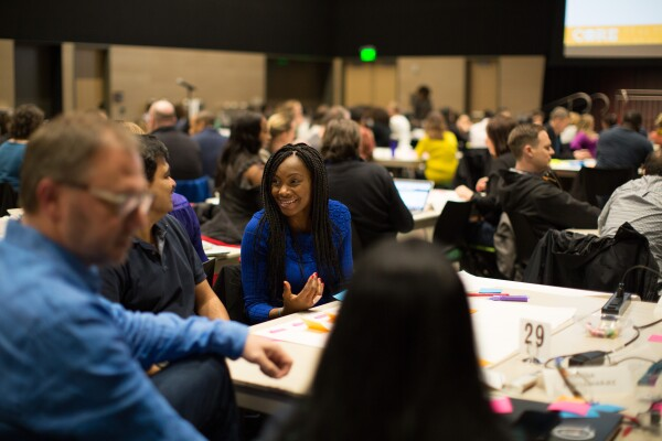 Diverse woman seated at a table in a conference room, is engaging in conversation with other conference attendees.