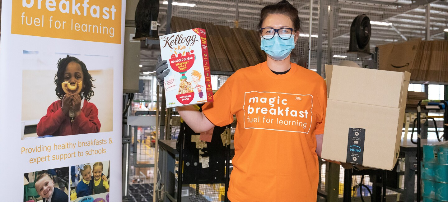 Amazon employee stood with a box filled with goods for Magic Breakfast