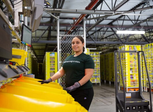 A woman working at an Amazon fulfillment center stands in front of a row of yellow bins.