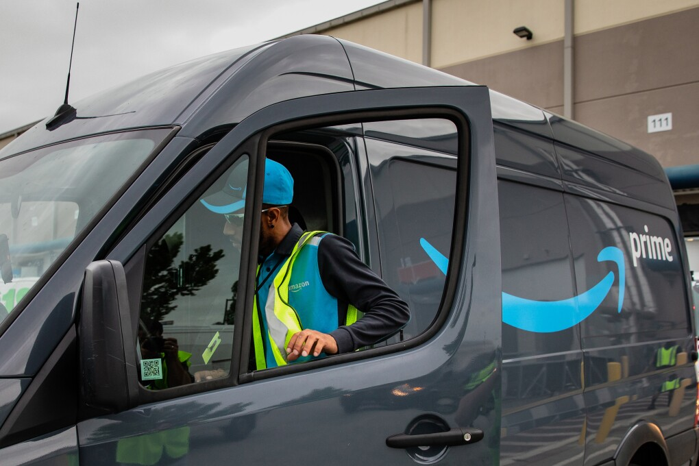 "A driver slides behind the wheel of a cargo van decorated with an Amazon smile logo and the word ""prime."""