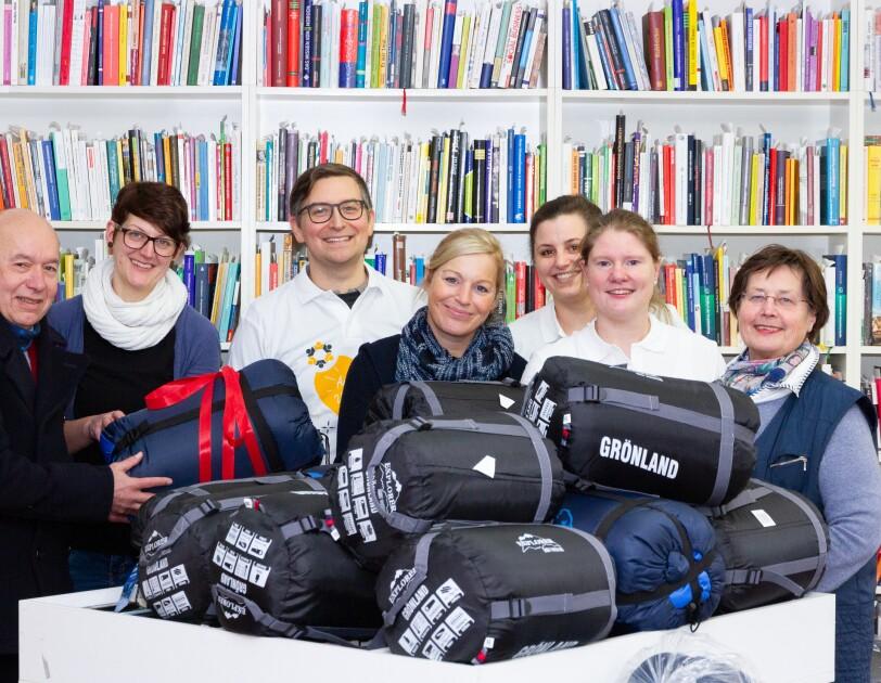 Verschiedene Personen stehen vor einem Stapel von Polar-Schlafsäcken