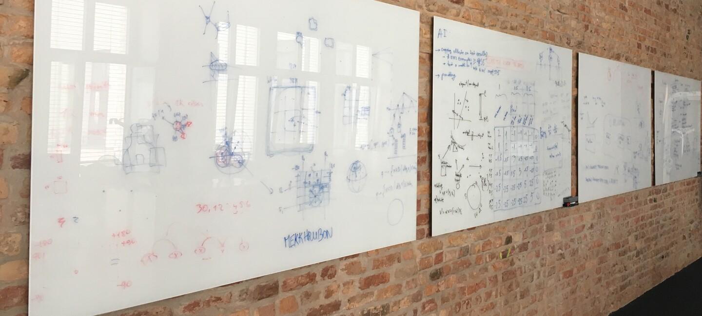 An an einer Wand hängen viele Whitebaords mit bunten Zeichnugnen, Notizen, Formeln und Stichpunkten.